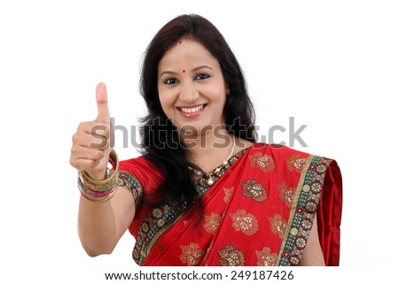 Cheerful traditional young Indian woman showing thumbs up against white background - stock photo