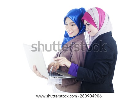 Cheerful two beautiful muslimah business women working on a laptop with hands typing keyboard and point at laptop screen - stock photo