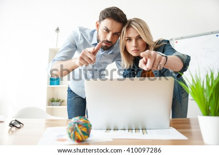Cheerful two colleagues are relating to work with seriousness - stock photo