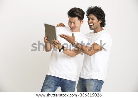 Cheerful two college students fun with digital tablet over white background - stock photo