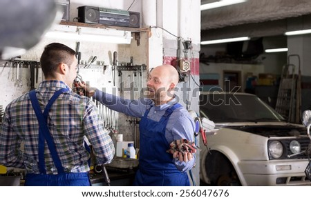 Cheerful two male workers in overalls working in the garage. - stock photo