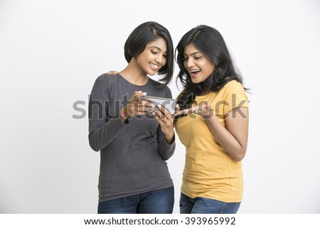 Cheerful two pretty young women watching in mobile phone - stock photo