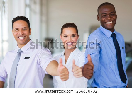 cheerful vehicle sales team giving thumbs up - stock photo