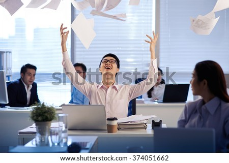 Cheerful Vietnamese business executive throwing documents in the air