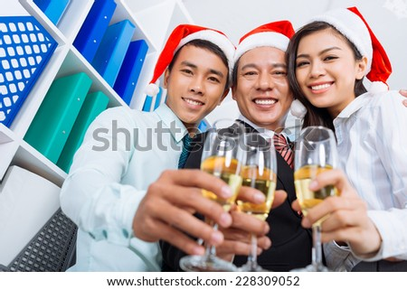Cheerful Vietnamese coworkers clinking glasses with champagne in the office