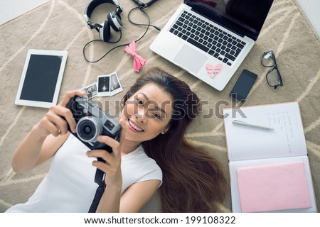 Cheerful Vietnamese girl lying on the floor  with her camera in hands - stock photo