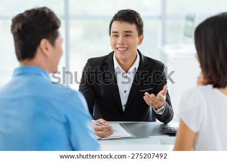 Cheerful Vietnamese sales manager giving advice to his clients - stock photo