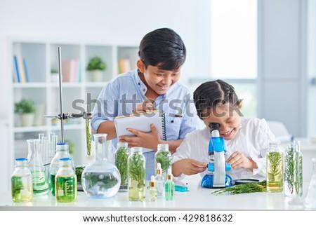 Cheerful Vietnamese school children working in pair in biology class - stock photo