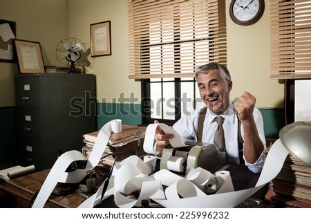 Cheerful vintage accountant surrounded by adding machine paper tape in his office. - stock photo