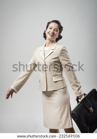Cheerful vintage woman smiling and walking with briefcase - stock photo