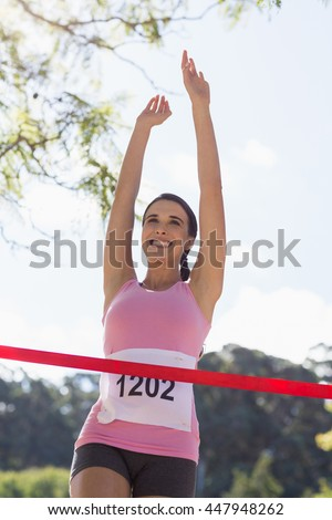 Cheerful winner female athlete crossing finish line in park - stock photo