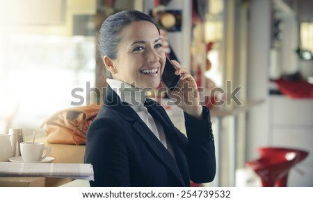 Cheerful woman at the bar phone calling and having a coffee break - stock photo