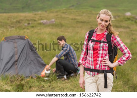 Cheerful woman carrying backpack while boyfriend is pitching tent in the countryside