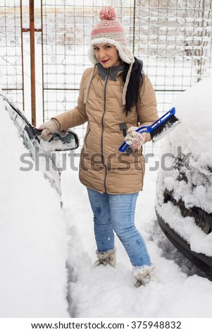 Cheerful woman cleaning snow from car in cold day