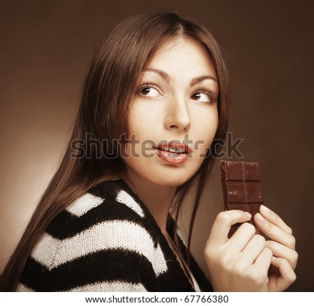 Cheerful woman eating chocolate - stock photo