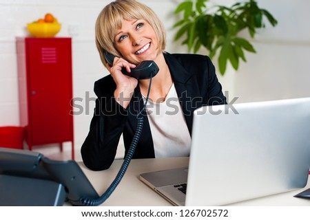 Cheerful woman engaged in a jovial conversation, at office desk. - stock photo