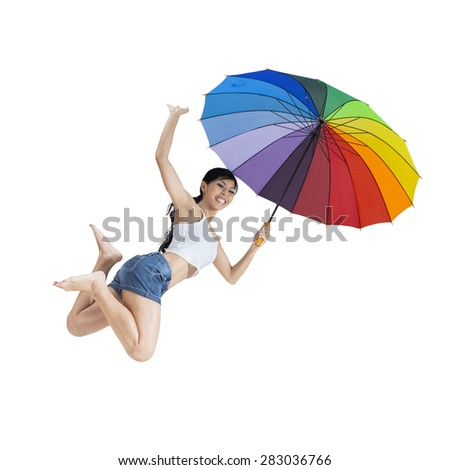 Cheerful woman enjoy freedom in the studio and jumping by holding a rainbow umbrella - stock photo