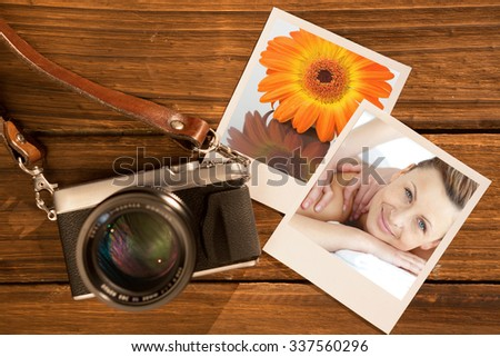 Cheerful woman enjoying a back massage against close up of an orange gerbera on a mirror - stock photo