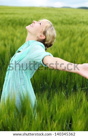 Cheerful woman enjoying the fresh air in cornfield - stock photo