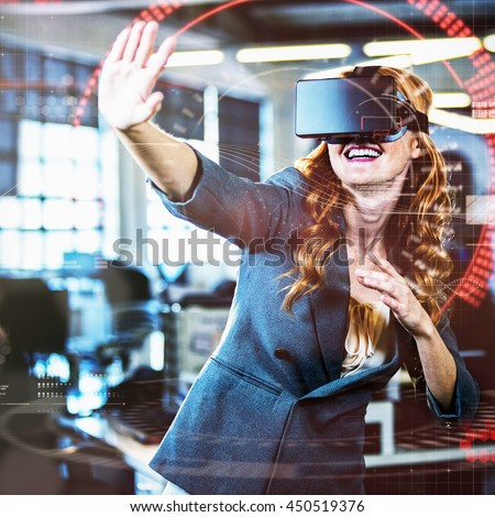 Cheerful woman gesturing while using virtual reality simulator in office - stock photo