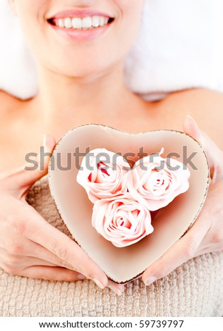 Cheerful woman holding a bowl in the shape of a heart with flowers in a spa center - stock photo