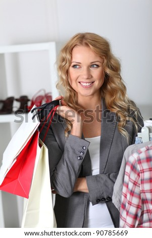 Cheerful woman holding shopping bags - stock photo