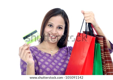 Cheerful woman holding shopping bags and credit card  against white background - stock photo