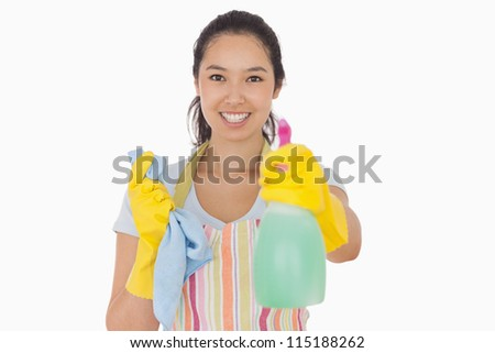 Cheerful woman holding up spray bottle in rubber gloves and apron - stock photo