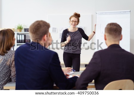 Cheerful woman in casual wear and eyeglasses at large flip chart during staff meeting with male and female co-workers - stock photo