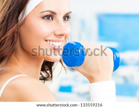 Cheerful woman in fitness wear exercising with dumbbell, at fitness center or gym - stock photo
