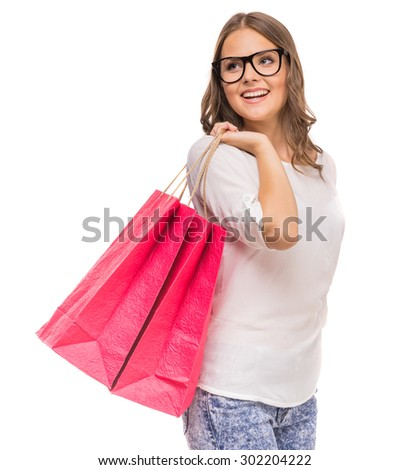 Cheerful woman in glasses holding colored shopping bags and looking away on white background. - stock photo