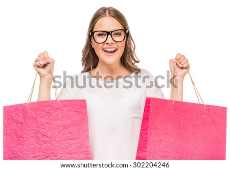 Cheerful woman in glasses holding colored shopping bags on white background. - stock photo