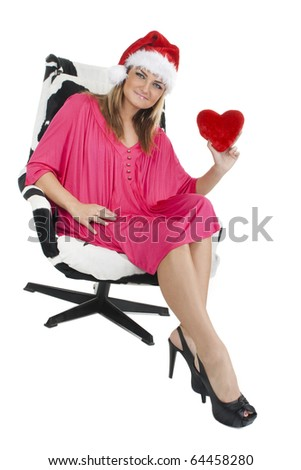 Cheerful woman in Santa hat and pink dress holding a plush heart