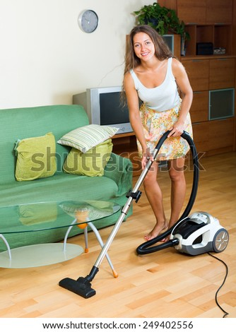 cheerful  woman in skirt cleaning with vacuum cleaner on parquet floor at home