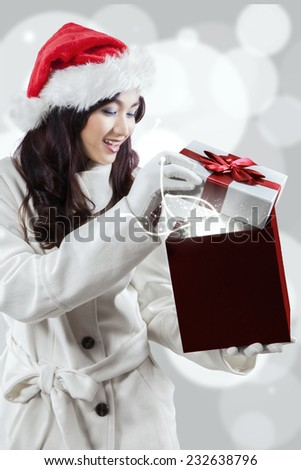 Cheerful woman in winter coat and wearing christmas hat, opening a presents with miracle light - stock photo