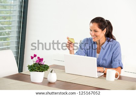 Cheerful woman internet home banking card laptop online shopping - stock photo