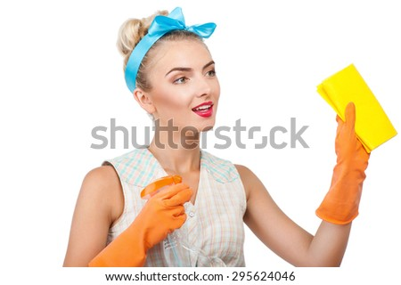 Cheerful woman is cleaning something with wisp and spray attentively. She is smiling and looking at it with interest. Isolated on background - stock photo