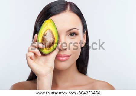 Cheerful woman is holding an avocado and covering her eye with it. She is looking at the camera and gently smiling. Her shoulders are naked. Isolated on background - stock photo