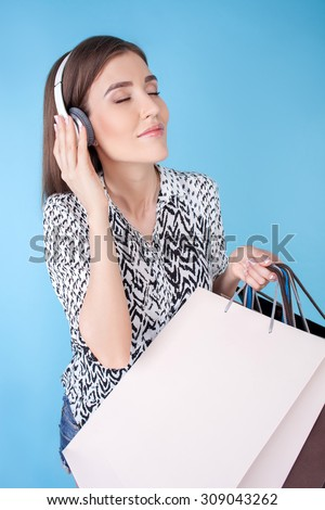 Cheerful woman is standing and holding packets of bought clothing. She is listening to music from earphones and smiling. The lady closed her eyes with enjoyment. Isolated on blue background - stock photo