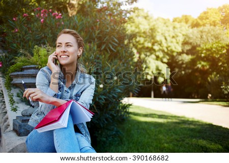 Cheerful woman is talking on mobile phone with her friend while is sitting with notepad in park in spring day,smiling happy female is enjoying pleasant cell telephone conversation during rest outdoors - stock photo