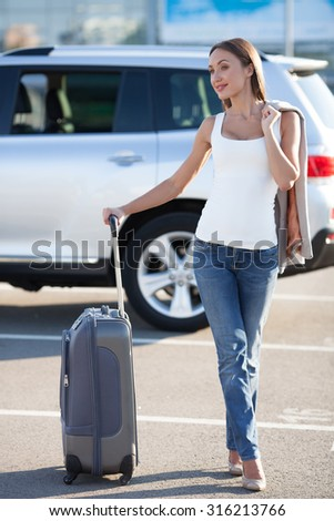 Cheerful woman is waiting for her flight at the airport. She is standing near her car with suitcase. The lady is posing and smiling. She is holding her jacket behind her back