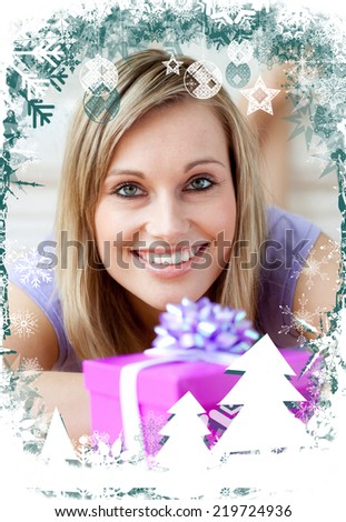 Cheerful woman looking at a gift against christmas themed frame - stock photo