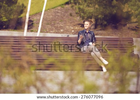 Cheerful woman on a bench with mobile phone and coffee - stock photo