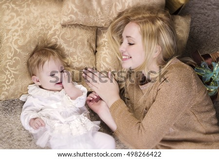 Cheerful woman playing with baby girl. The concept of family and love