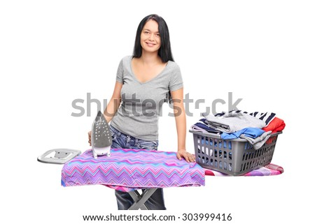 Cheerful woman posing behind an ironing board with a laundry basket full of clothes on it isolated on white background - stock photo