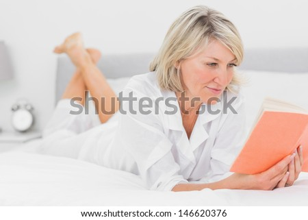Cheerful woman reading a book lying on bed at home in bedroom - stock photo