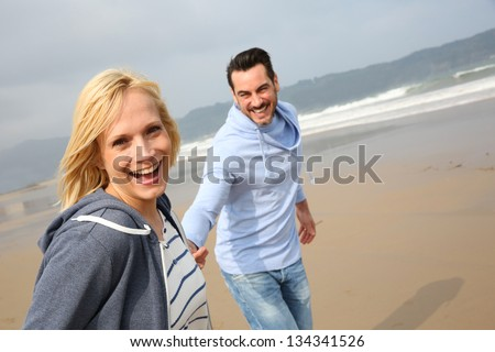 Cheerful woman running with husband on the beach - stock photo