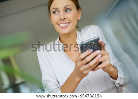 Cheerful woman sending message with smartphone