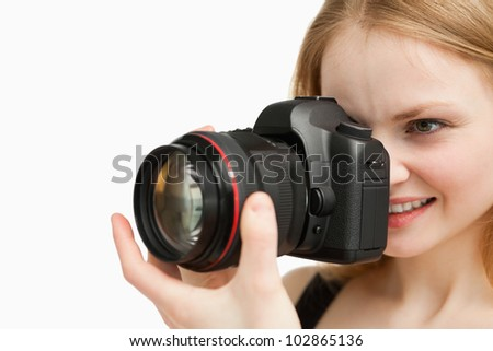 Cheerful woman shooting with a camera against white background - stock photo