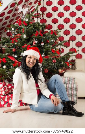 Cheerful woman sitting in front of Christmas tree home - stock photo